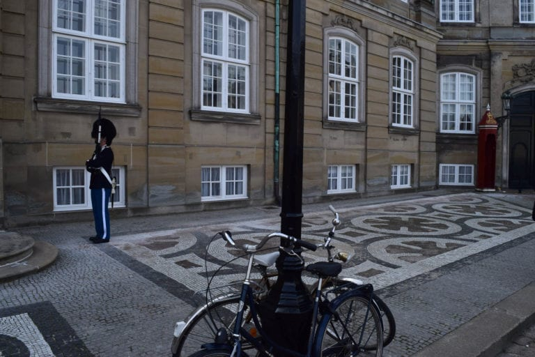 Danish bikes and guard with fuzzy hat.